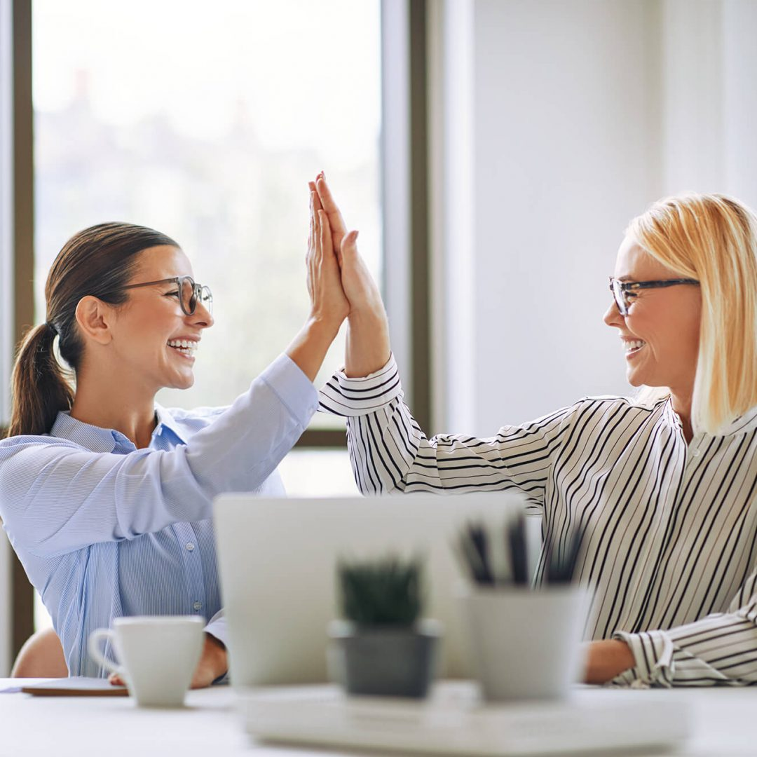 two-smiling-businesswomen-high-fiving-together-in-DDNACN5 (1)